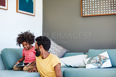 Buy stock photo Shot of a cheerful young father and his son browsing on a digital tablet while being seated on a couch at home