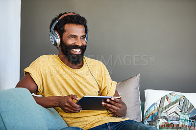 Buy stock photo Shot of a focused young man listening to music through headphones while being seated on a couch at home