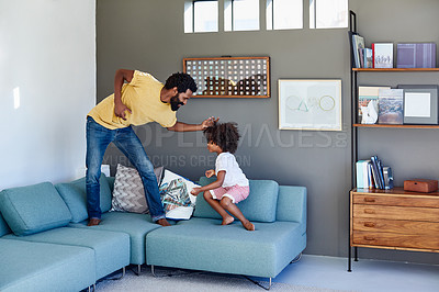 Buy stock photo Shot of a cheerful young father and his son dancing on a couch while listening to music at home during the day