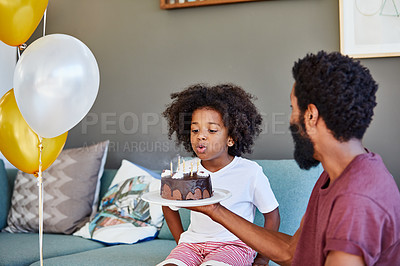 Buy stock photo Shot of a cheerful little boy blowing out candles on a cake that he received from his dad inside at home during the day