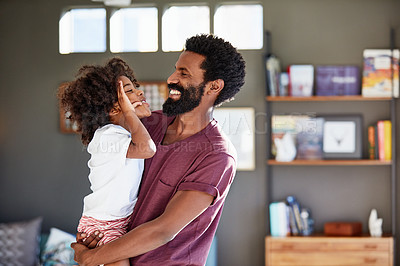 Buy stock photo Shot of a cheerful young father holding his son while looking at each other inside at home during the day