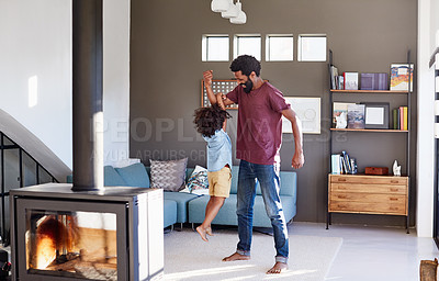 Buy stock photo Shot of a cheerful young man picking up his son with his one arm inside at home during the day