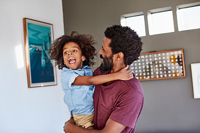 Buy stock photo Shot of a cheerful young man holding his son in his arms while standing in the living room at home during the day