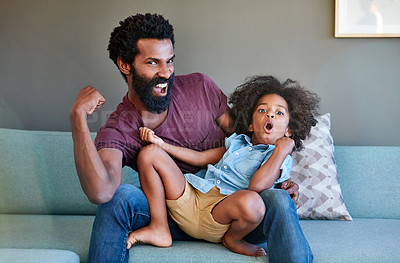 Buy stock photo Portrait of a cheerful father and son striking a pose while being seated on the couch at home during the day