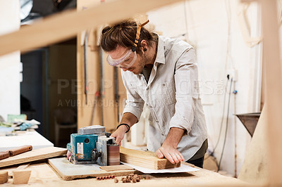 Buy stock photo Shot of a man working with wood in a furniture manufacturing workshop