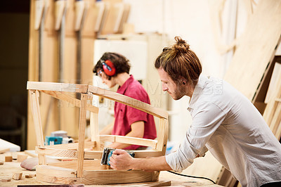 Buy stock photo Shot of two people working with wood in a furniture manufacturing workshop