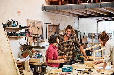 Buy stock photo Shot of three people working with wood in a furniture manufacturing workshop