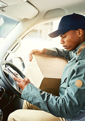 Buy stock photo Shot of a courier using a cellphone while sitting in a delivery van