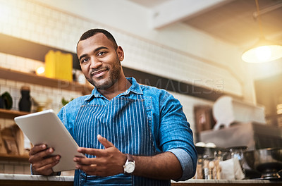 Buy stock photo Cropped portrait of a handsome young man working on a tablet in his coffee shop