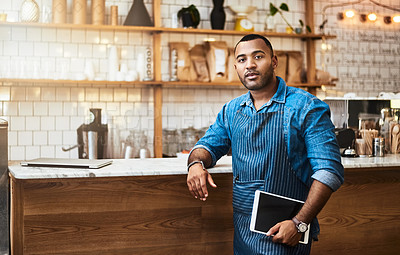 Buy stock photo Cropped portrait of a handsome young man holding a tablet while working in his coffee shop