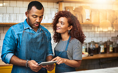 Buy stock photo Cropped shot of an affectionate young couple working on a tablet in their coffee shop