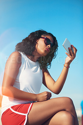 Buy stock photo Cropped shot of an attractive young woman taking a selfie outside