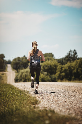 Buy stock photo Rearview shot of a young woman out on a trail run