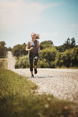 Buy stock photo Shot of a young woman out on a trail run