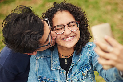 Buy stock photo Cropped shot of a teenage couple taking a selfie outdoors