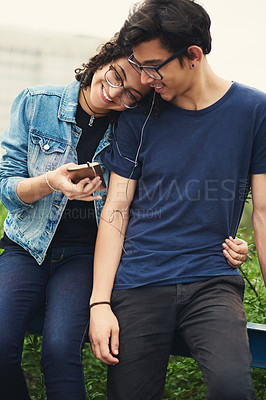 Buy stock photo Cropped shot of a teenage couple listening to music together outdoors
