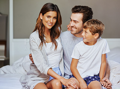Buy stock photo Portrait of a cheerful young family seated on bed while holding each other and looking at the camera at home in the morning