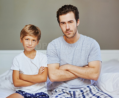 Buy stock photo Portrait of a confident father and son seated on a bed with arms folded while looking at the camera at home in the morning