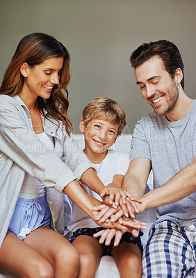 Buy stock photo Shot of a cheerful young family forming a huddle with their hands while being seated in the bedroom at home in the morning