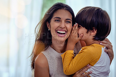 Buy stock photo Shot of an adorable little boy whispering into his mother's ear