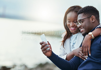 Buy stock photo Shot of an affectionate young couple using a cellphone together outdoors