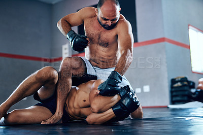 Buy stock photo Shot of a male fighter about to punch another male fighter while in combat on the floor at the gym