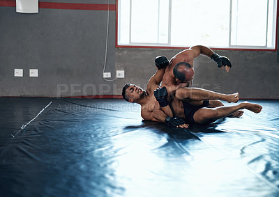 Buy stock photo Shot of two male fighters wrestling on the floor at the gym