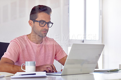 Buy stock photo Cropped shot of a handsome businessman working on his laptop in his office