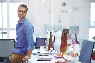 Buy stock photo Shot of a handsome young businessman in his office
