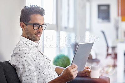 Buy stock photo Cropped shot of a handsome businessman using his digital tablet at home
