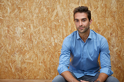 Buy stock photo Cropped shot of a handsome young man posing against a wooden background