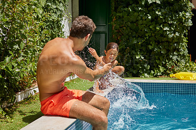 Buy stock photo Shot of a father and son splashing each other at the swimming pool