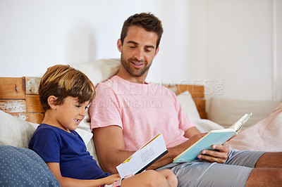 Buy stock photo Shot of a father and son reading and relaxing on the sofa at home