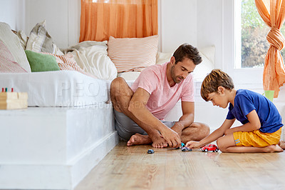 Buy stock photo Shot of a father and son playing with toy cars together in the living room at home