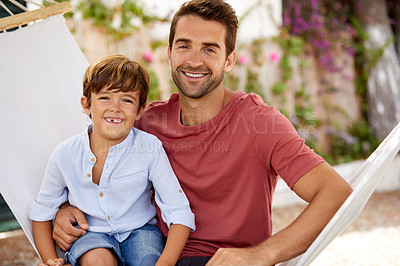 Buy stock photo Portrait of a father and son relaxing together on a hammock outside