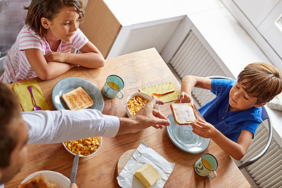 Buy stock photo High angle shot of a young family having breakfast together at home