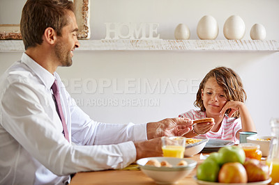 Buy stock photo Cropped shot of a young family having breakfast together at home