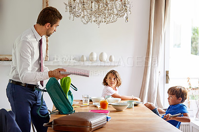 Buy stock photo Cropped shot of a young siblings having breakfast while their father gets their backpacks ready for school