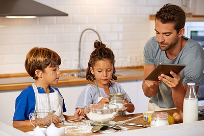 Buy stock photo Cropped shot of a father helping his son and daughter bake at home