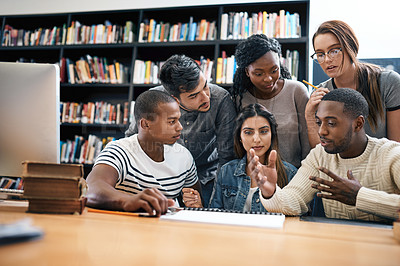Buy stock photo Shot of a group of young students working on an assignment together in a college library