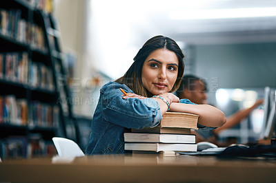 Buy stock photo Shot of a young woman resting on a pile of books in a college library and looking thoughtful