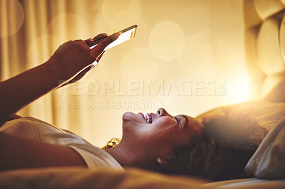 Buy stock photo Shot of a young woman using a cellphone in bed at night