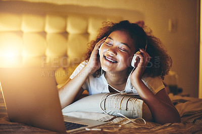 Buy stock photo Shot of a young woman wearing headphones while listening to music from her laptop at home