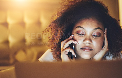 Buy stock photo Shot of a young woman talking on a cellphone while using a laptop at home