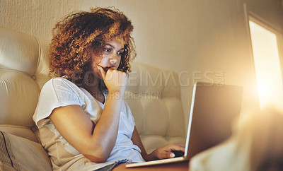 Buy stock photo Shot of a young woman using a laptop while sitting on her bed at home