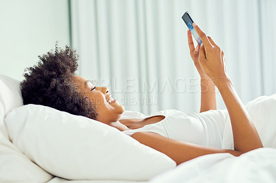 Buy stock photo Cropped shot of an attractive young woman using a cellphone in bed at home