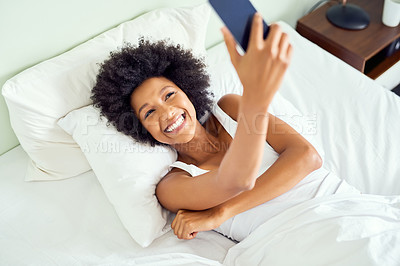 Buy stock photo Cropped shot of an attractive young woman taking a selfie in bed at home