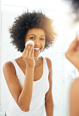 Buy stock photo Cropped shot of an attractive young woman wiping her face with a cotton pad in the bathroom at home