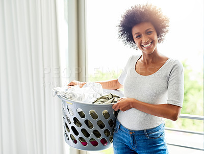 Buy stock photo Cropped shot of an attractive young woman holding a washing basket at home