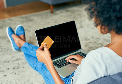 Buy stock photo High angle of an unrecognizable young woman using her laptop to shop online at home over the weekend